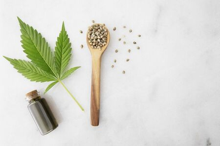 Small bottle of CBD oil with cannabis leaf and seeds in a wooden spoon, viewed from directly above.