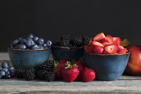 Fresh strawberreis, blueberries and blackberries in blue bowls surrounded by fruit.
