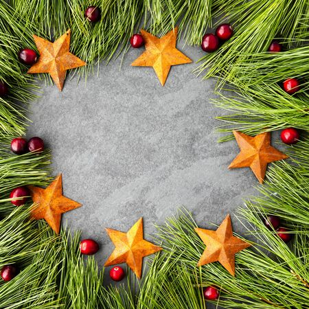 Pine boughs, stars and cranberries rustic Christmas themed frame with slate copy space area. Great for social media.