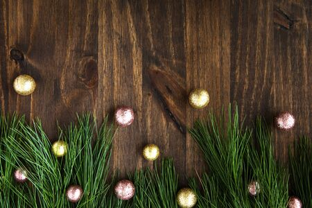 Pine boughs with christmas decorations on wooden surface with copy space.