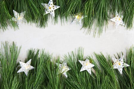 Pine boughs and star lights on marble surface with copy space in the middle.