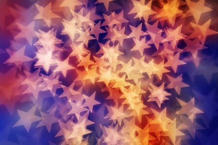 Star shaped bokeh background in yellow, reds and purple tones.