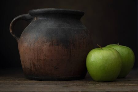 Two granny smith apples with old pottery jug.  Shot at eye level with dark rustic feel.