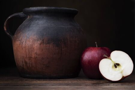 Two red apples, one whole one cut, with old pottery jug.  Shot at eye level with dark rustic feel.