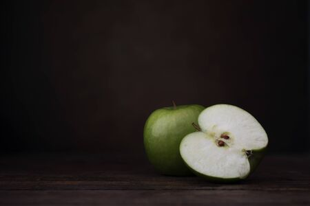 Two granny smith apples, one whole and one cut in half.  Two granny smith apples with old pottery jug.  Shot at eye level with dark rustic feel and copy space/