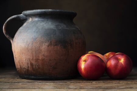 Fresh nectarines next to a rustic pottery jug, on  a wooden table with a dark background