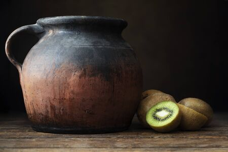 Fresh kiwi, both whole and sliced, on wooden table with rustic pottery jug