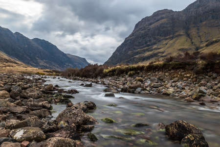 Glencoe river with smooth water flow and cloudy day. hill views at the back