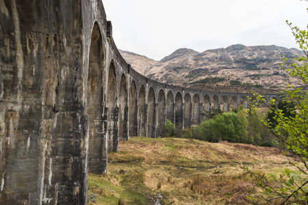 Old train railway with arched bridge surrounded by trees with hills in view, Glennfinnan Viaduct, Scottish Highlands. Spring time of the year Archivio Fotografico