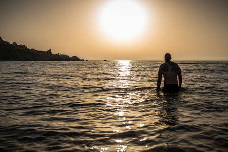 Mascular man relaxed in the water during sunset with nobody swimming around silhouette. Back View Horizontal