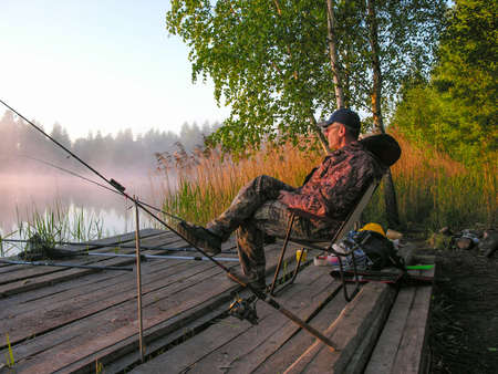 meets: Fisherman meets sunrise on the bank of forest lake