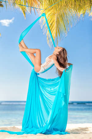 relaxing girl in aerial silk on the beach