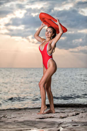 sexy girl in baywatch outfit at sundown on the beach