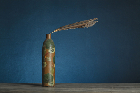 Red paint bottle with feather on blue background  still life   photo