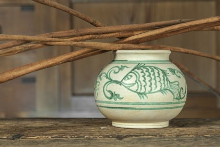Antique ceramic paint bowl with stick on cabinet wooden background (Still life) photo