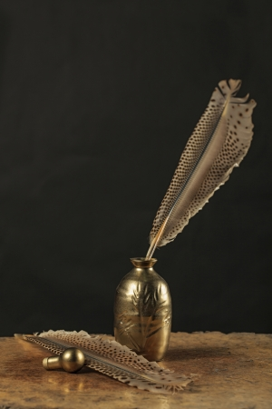 Golden inkstand with quill on wooden table in dark background  Still life