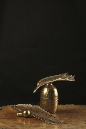 inkstand: Golden inkstand with quill on wooden table in dark background  Still life