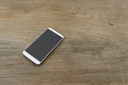 Phone display crack isolated on wooden table photo