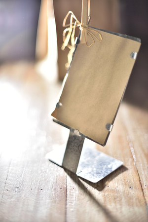 nip: Classic Recycle paper tag in front of iron stand on wood table (Low light)