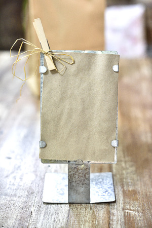 nip: Classic Recycle paper tag in front of iron stand on wood table