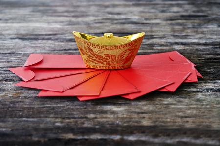 """lingotto d'oro cinese con busta rossa """"Ang Pao"""" sulla tabella di legno"""