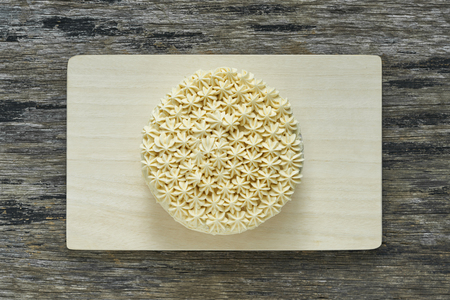 Butter cream cake on wood plate