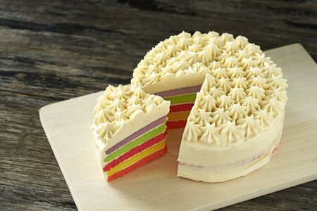 Colorful butter cream cake on wood plate slice