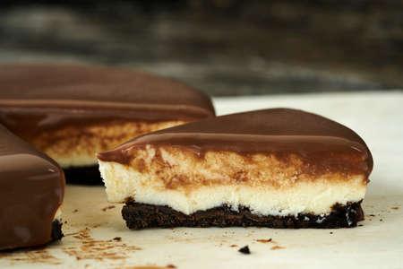 Chocolate cheesecake slice on wood plate