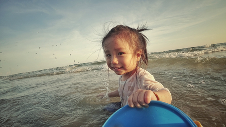 The girl play in the sea with sand bucket (Action Camera)