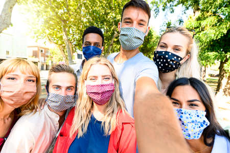 Multiracial young people taking selfie while wearing protective masks - New normal summer friendship concept with young people having fun together - Warm filter