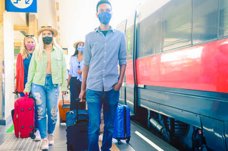 Group of trendy multiracial friends with face mask walking in train station with the baggage - New normal travel concept