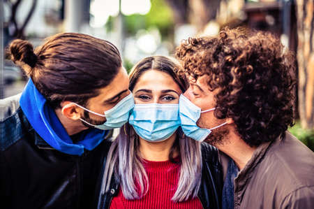 Double kiss with medical protective mask on face for fear of virus infection - Young millennials friends wearing protective face masks and kissing each other on the cheek - Concept about virus spread prevention
