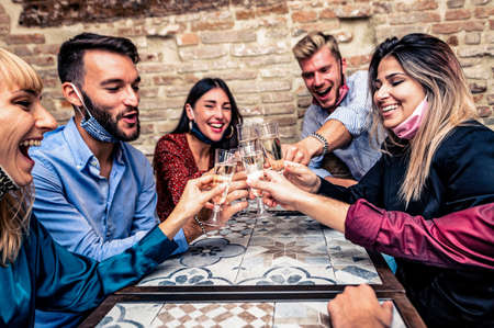 Christmas party! Young people with face mask toasting with champagne flutes in coronavirus time - Multiethnic friends congratulating each other on the new year eve - Celebration and nightlife, holiday background, selective focus Stock fotó