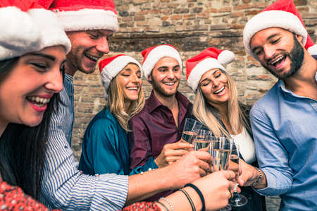 Merry Christmas and Happy New Year! Young freinds are celebrating holidays in hause - Group of young entrepreneurs are drinking champagne in coworking, wearing xmas cap - Lifestyle concept
