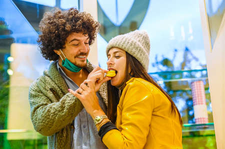 Beautiful happy couple feed each other in pastry shop - The young man feeds a macarons to his girlfriend - New normal lifestyle concept in covid-19 time Stock Photo