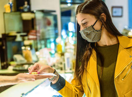 Happy female customer with face mask, taking one chocolates from man or barman at pastry - Good dessert - New normal lifestyle concept about sweet life in covid-19 time