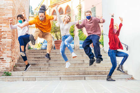 Happy crazy friends with face mask jumping down the stairs in the city street in corona virus time - Teenagers come out of school - New normal lifestyle concept - Main focus on blonde girl