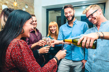 Young people pour champagne and celebrate birthday - Group of young coworkers celebrate and toast for success - Selective focus