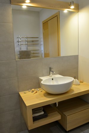 Grey stone pattern tiled contemporary bathroom interior design with minimal natural wood furniture details dominate neutral colors. White ceramic washbasin on a wooden surface