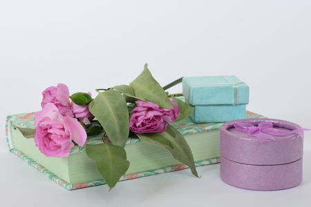 Provence style composition on white background: notebook, pink flowers and violet and mint color gift boxes Archivio Fotografico