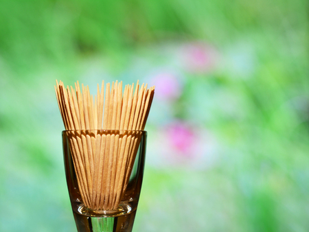 Wooden toothpicks in a glass container on a green background