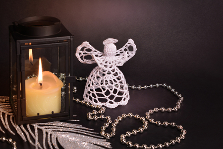Christmas decorations on black background. White crochet angel, lantern, candle, silver feather and beads