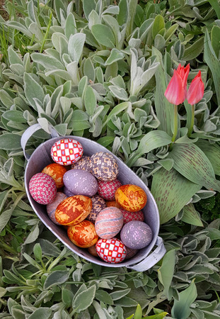 Top view of Easter decorated eggs in a vintage metal basket in a flower garden
