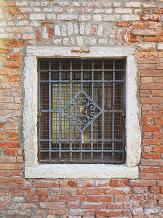 Old grated window in a brick wall in Venice city, Italy