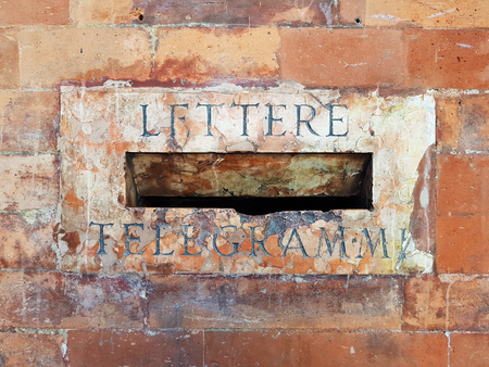 Old mailbox slot for letters and telegrams in a brick wall in Bologna city, Italy