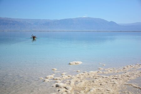 Tourists wade in the salty Dead Sea water 스톡 콘텐츠