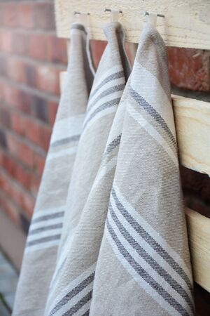 Striped rough heavy linen kitchen or hand towels hanging. Home textile. Selective focus 스톡 콘텐츠