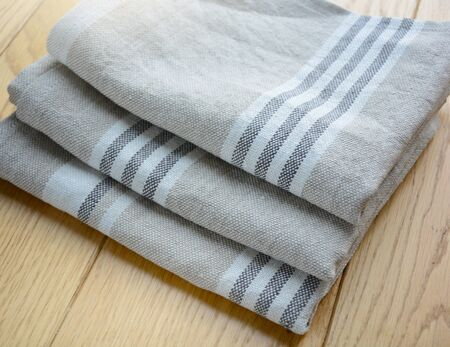 Striped rough heavy linen kitchen or hand towels on wooden background. Home textile