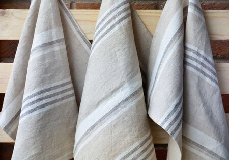 Striped rough heavy linen kitchen or hand towels hanging. Home textile 스톡 콘텐츠