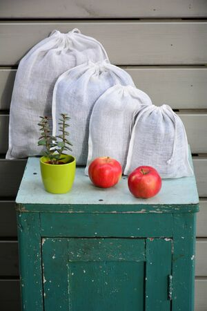 Reusable zero waste linen produce bags with apple fruits on old peeled closet